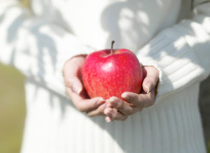 Woman Holding Red Apple --- Image by © Royalty-Free/Corbis