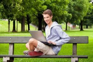Teenager mit Laptop im Freien