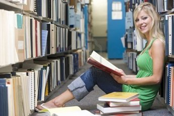 3201240-woman-sitting-on-floor-in-library-holding-book